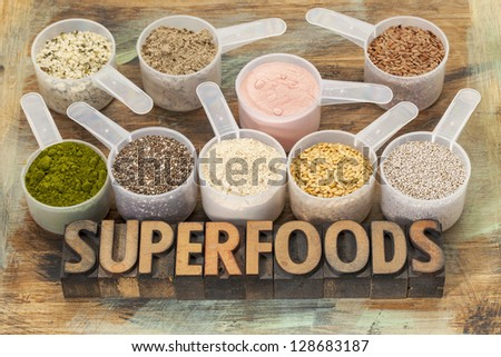 superfoods word in letterpress wood type with plastic scoops of healthy seeds and powders (chia, flax, hemp, pomegranate fruit powder, wheatgrass, maca root) - stock photo