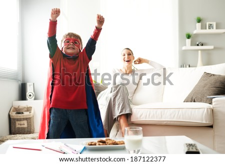 Superhero boy having an healthy snack with cookies and milk with his mother on background. - stock photo