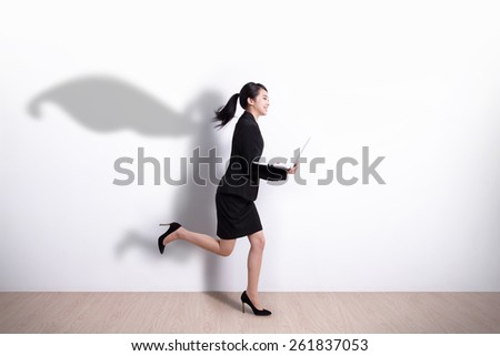 Superhero business woman running and hold laptop computer with white wall background, great for your design or text, asian - stock photo