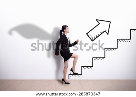 Superhero Business woman stepping up on stairs to gain her success with white wall background, asian - stock photo