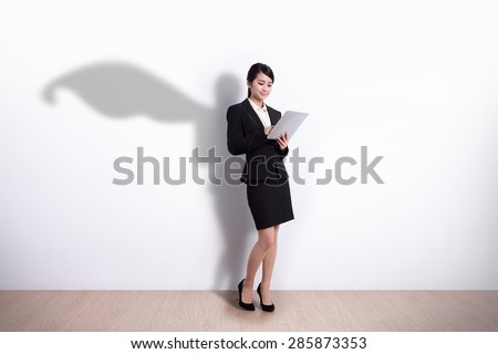 Superhero Business Woman using digital tablet pc computer with white wall background, great for your design or text, asian - stock photo