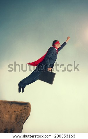 superhero businessman taking flight from a cliff ledge - stock photo