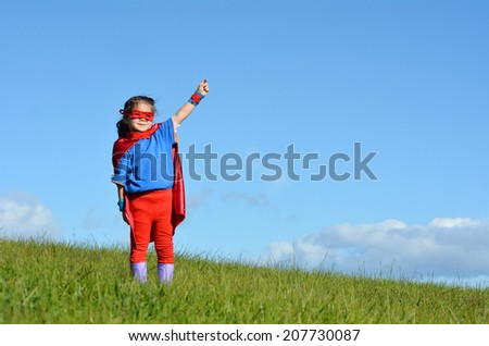 Superhero child (girl) against dramatic blue sky background with copy space. concept photo of Super hero, girl power, play pretend, childhood, imagination. - stock photo