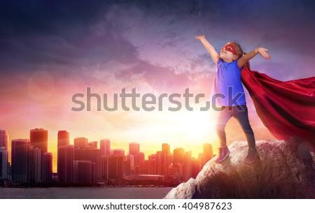 Superhero Child With Cityscape To Sunset - stock photo