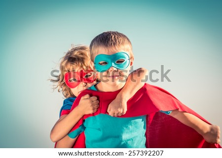 Superhero children against summer sky background. Kids having fun outdoors. Boy and girl playing. Success and winner concept - stock photo