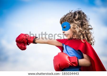 Superhero kid against dramatic blue sky background - stock photo