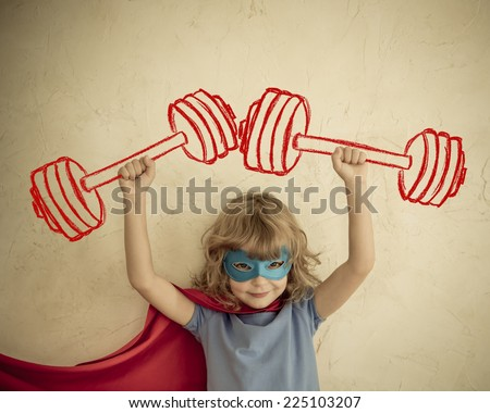 Superhero kid having fun at home. Retro toned - stock photo