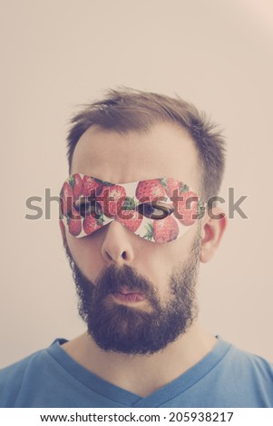 Superhero wearing mask with strawberries, making silly faces. Retro colors - stock photo