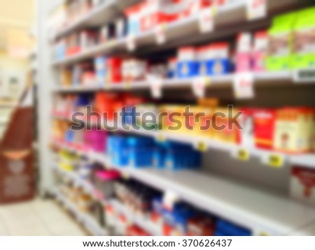 Supermarket shelves with first breakfast products like tea, coffee, barley, sugar. Blurred effect - stock photo