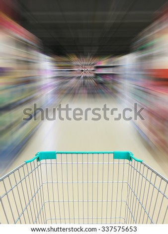 supermarket shopping cart view with supermarket aisle motion blur - stock photo