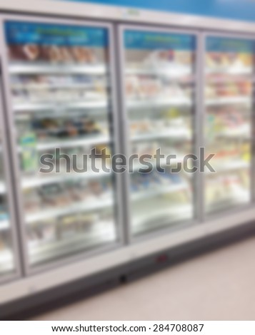 Supermarket store blur background with frozen food shelves in refrigerator - stock photo