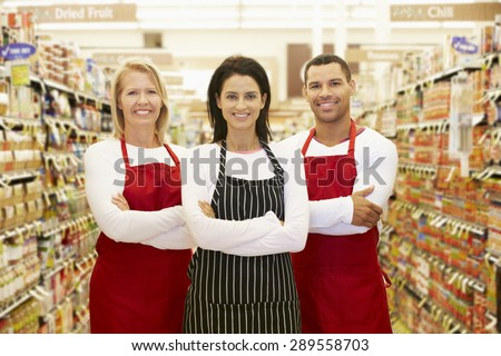 Supermarket Workers Standing In Grocery Aisle - stock photo