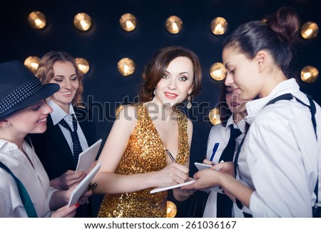Superstar woman wearing golden shining dress crowded by paparazzi - stock photo