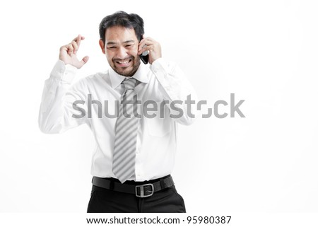 Superstitious - Asian business man with crossed fingers over white background - stock photo