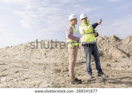 Supervisor examining construction site against sky - stock photo