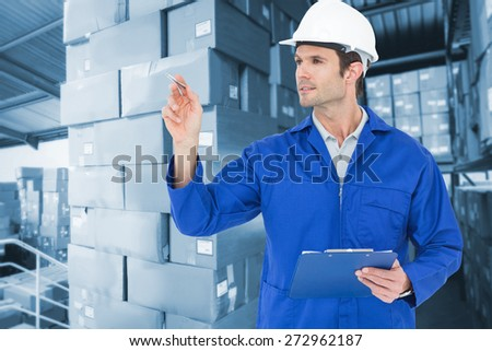 Supervisor inspecting while holding clip board against shelves with boxes in warehouse - stock photo