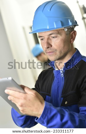 Supervisor on construction site using tablet - stock photo