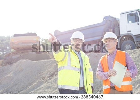 Supervisor showing something to colleague while discussing at construction site - stock photo