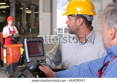 supervisor talking to forklift operator in warehouse - stock photo