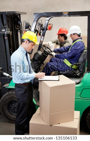 Supervisor writing on clipboard with foremen working at warehouse - stock photo