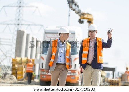 Supervisors discussing at construction site - stock photo