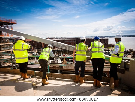 Supervisors overseeing a construction site - new industrial development - stock photo