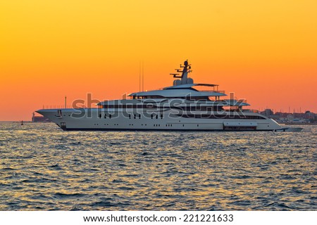 Superyacht on yellow sunset side view - stock photo