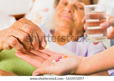 Supplements in nurse's hands for weak senior woman. - stock photo