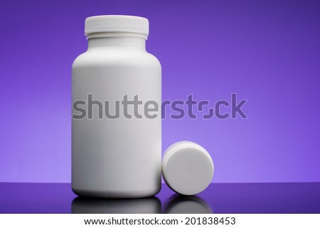 Supplements, medications or vitamin bottle on blue background - stock photo