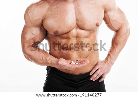 Supplements. Muscular Male holding various pills in his hand - stock photo