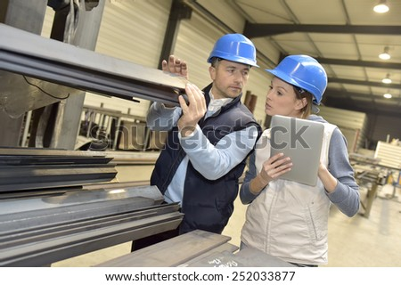 Supplier with engineer checking on production in factory - stock photo