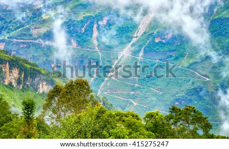 Supply dangerous winding road passes with dirt roads winding halfway up the mountain side without any corridor of protection. This beautiful stretch of road as well as in Ha Giang, Vietnam - stock photo