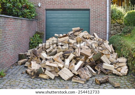 Supply of firewood, dumped in a garage driveway of a small house - stock photo