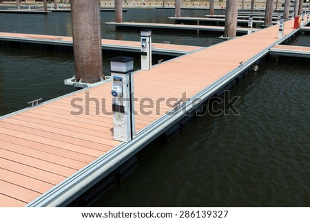 supply post for water, gas, electricity at the side of  footpath on a pier head with mooring cleats and berth of yacht marina on pontoons - stock photo