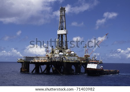 supply vessel along side drilling rig in offshore area during operation of supply - stock photo