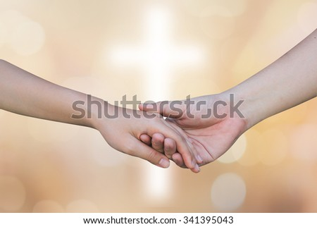 support and assistance of couple human hands over cross on golden background,helping hand concept.close up male and female hands touching together:faith,forgiveness,strength concept.connecting hand. - stock photo