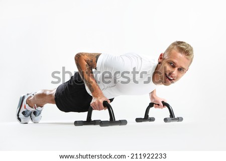 Support for push-ups . Attractive young man doing push-ups, tattooed in sports trousers  - stock photo