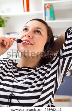 Support phone operator in headset at workplace. - stock photo