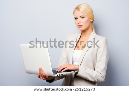 Supporting your business. Confident young businesswoman holding laptop while standing against grey background - stock photo