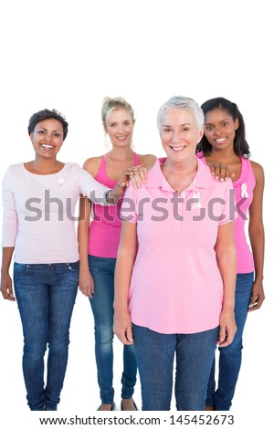 Supportive women wearing pink tops and breast cancer ribbons on white background - stock photo