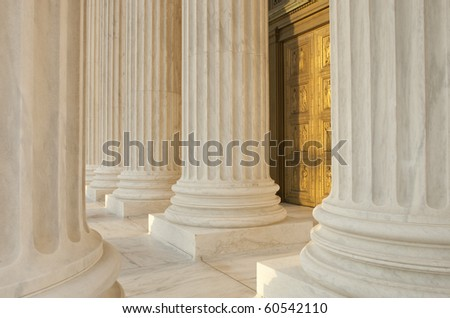 Supreme Court Column Details. Sunset orange light cast across scene. - stock photo