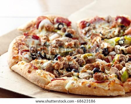 supreme pizza on a cardboard box - stock photo