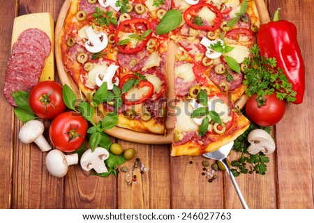 Supreme Pizza with tasty slice on wooden table background - stock photo