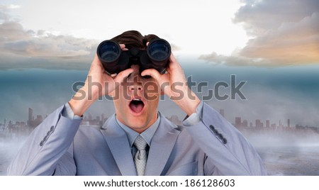 Suprised businessman looking through binoculars against cityscape on the horizon - stock photo