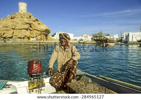 SUR - OMAN - DEC 1, 1992: man offers his ferry services to travelers in Sur, Oman. Sur is known for being an important destination point for sailorssince the 6th century. - stock photo