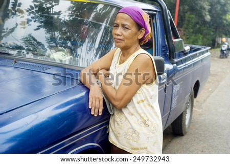 SURABAJA, INDONESIA - APRIL 22, 2012: Portrait of  unidentified indonesian woman near a car. About 37 million people are under the poverty line representing 17% of the entire population. - stock photo
