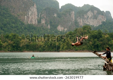 SURATTHANI,THAILAND-APRIL 5 : Traveller jumping in fun and happiness on Cheow Larn lake (Khao Sok National park) on April 5,2014 in Surat Thani Province ,Southern of Thailand. - stock photo