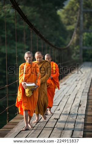 SURATTHANI, THAILAND - MARCH 15 : Unidentified Buddhist monks walk for people offering food on Mach 15, 2012 in Suratthani, Thailand.  Offering food is one of most common rituals in Buddhism. - stock photo