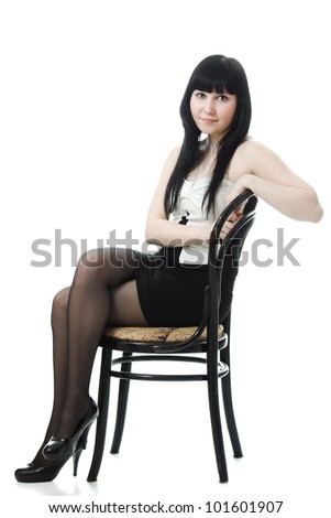 Sure beautiful woman in evening dress sitting on a chair on a white background - stock photo