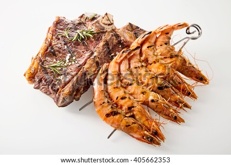 Surf and turf marinated spicy T-bone beef steak and skewered queen prawns seasoned with rosemary, high angle view on white - stock photo